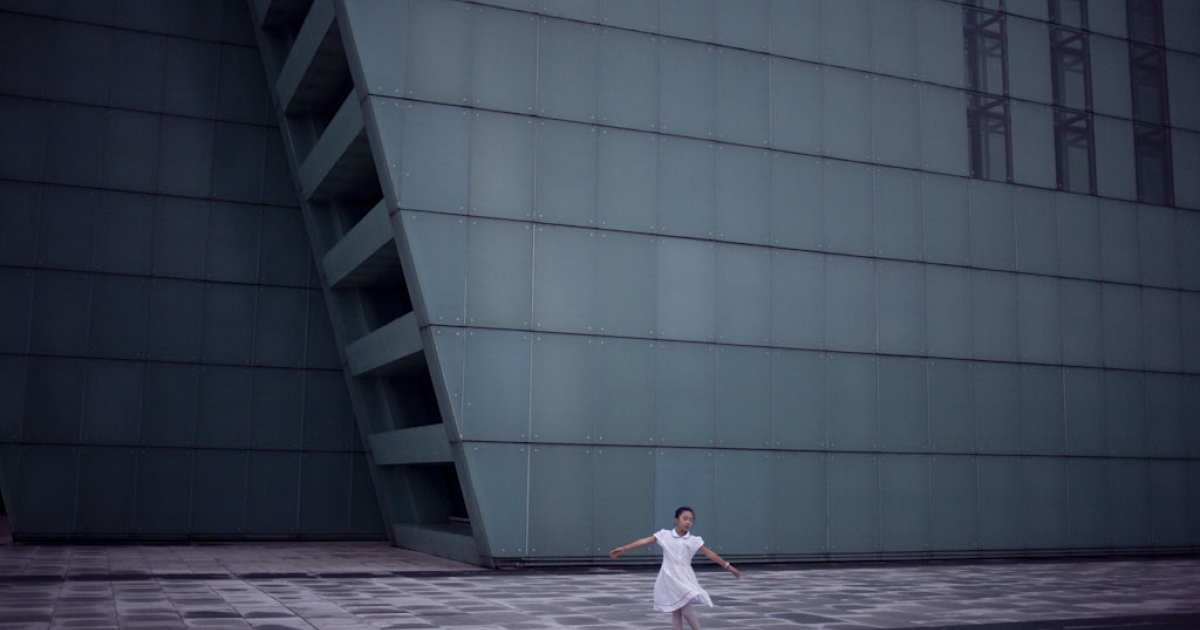 A girl dances in front of Chongqing's newly constructed Grand Theater.</p>
