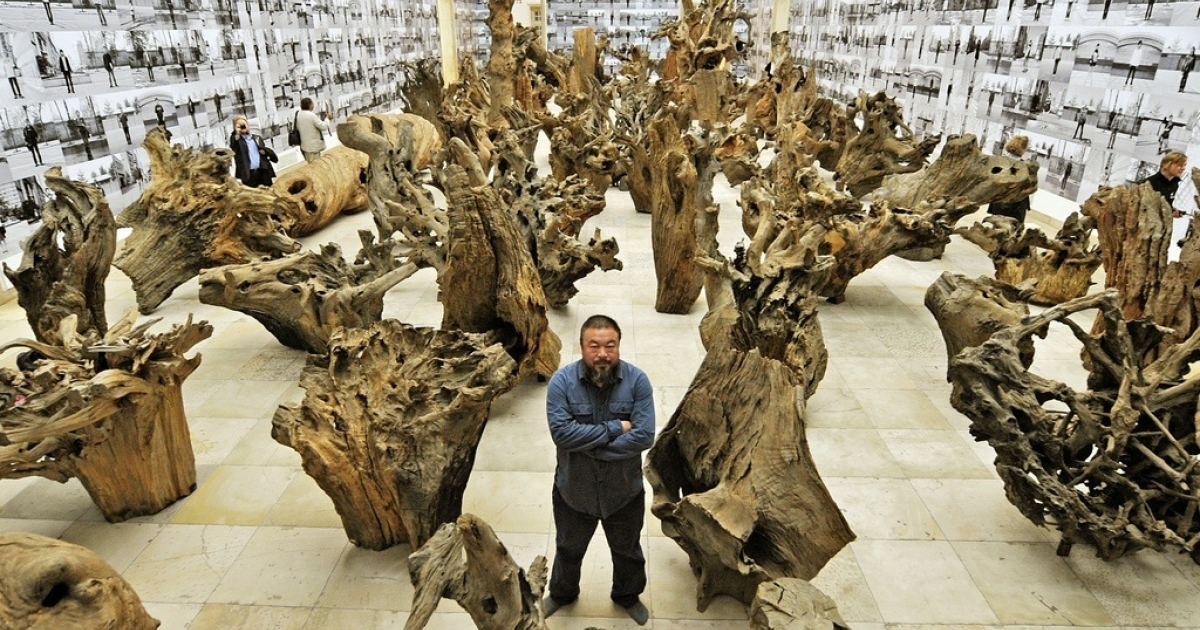 Chinese artist Ai Weiwei poses in the middle of his work made of 100 pieces of trees and called