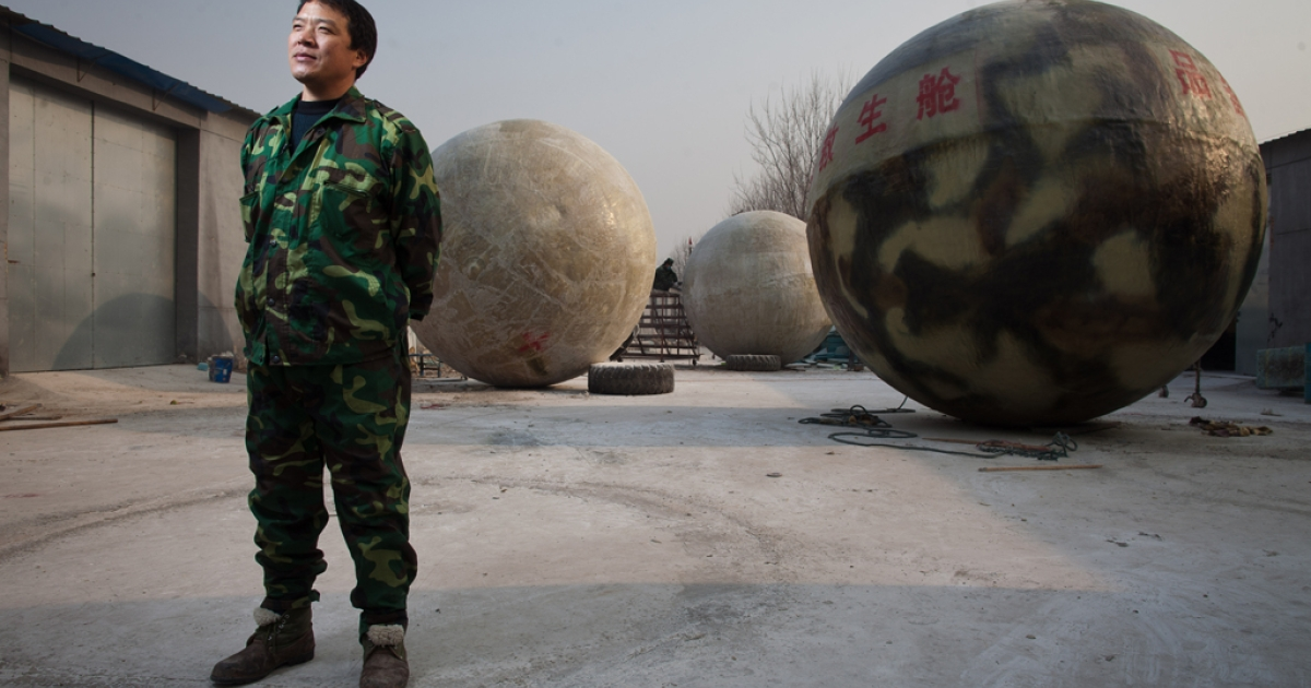 Farmer Liu Qiyuan poses among survival pods he built in the village of Qiantun, Hebei province, south of Beijing on Dec. 11, 2012. Inspired by the apocalyptic Hollywood movie