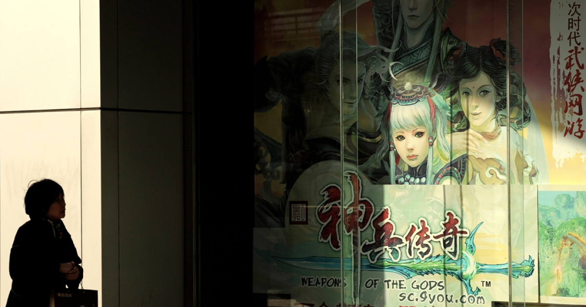 A woman walks past a billboard showing characters of a Chinese-developed online video game.</p>