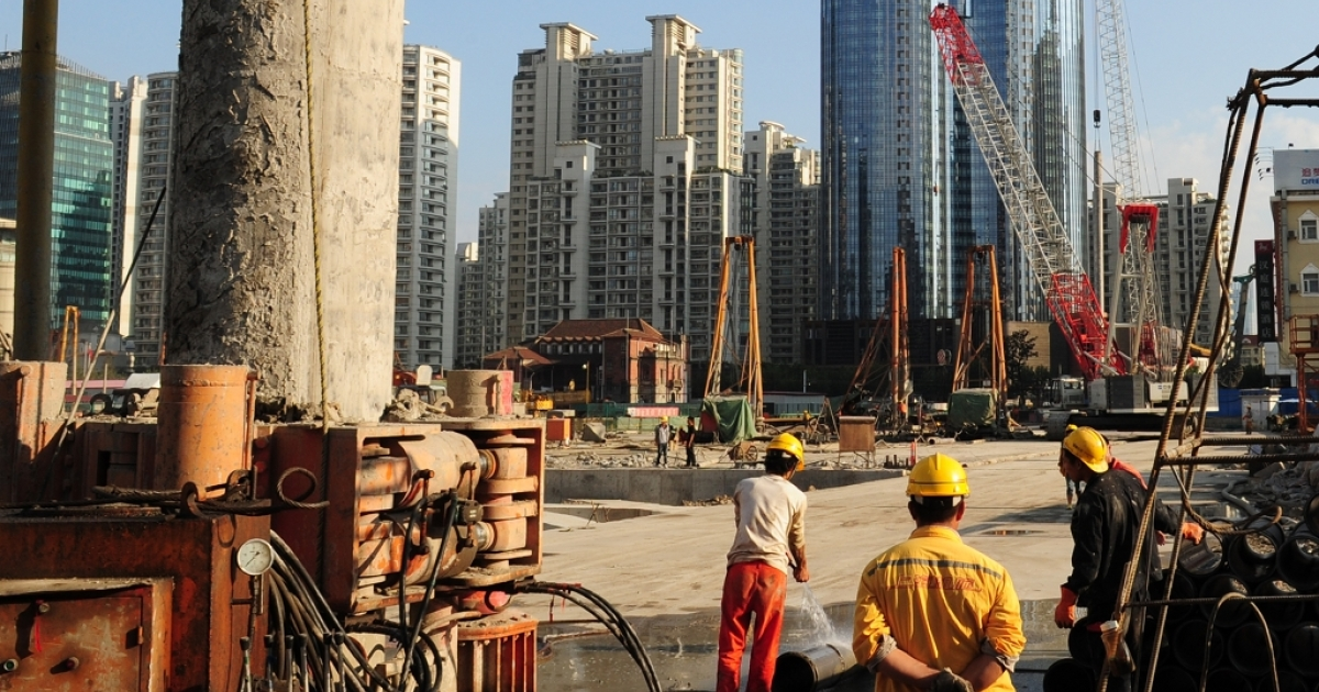 Laborers work at a new property development under construction on the busy Nanjing Road shopping street in Shanghai. Huge increases in real estate opportunites and construction have fed much of China's foreign direct investment.</p>
