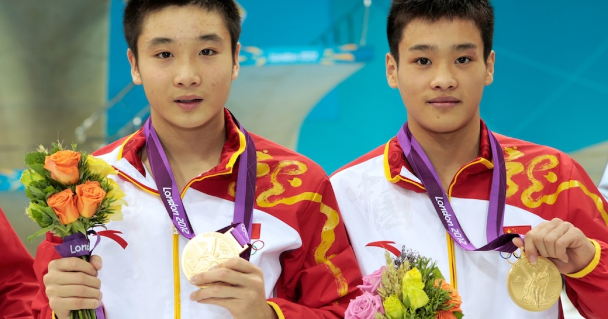 Cao Yuan and Zhang Yanquan of China celebrate with their gold medals during the medal cermony for the men's synchronized 10m platform diving at the London 2012 Olympic Games at the Aquatics Centre on July 30, 2012 in London.</p>