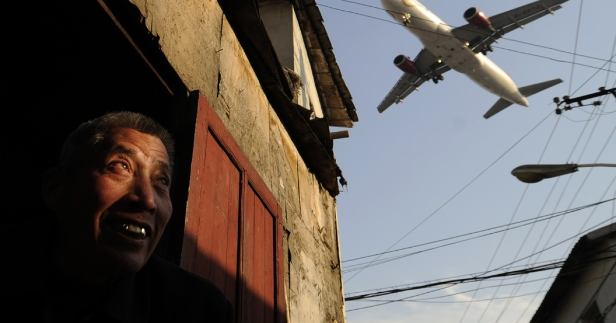 A man watches as an airliner flies over his house into Hongqiao International airport in Shanghai on January 5, 2012. Chinese airlines will not pay a charge on carbon emissions imposed by the European Union from January 1, a national aviation industry group said as the cap-and-trade scheme, which has angered the US and Chinese governments and airlines worldwide, came into force after the EU's highest court rejected a challenge brought by US carriers last month.</p>