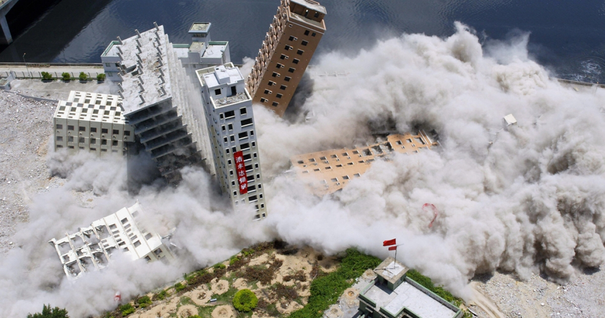 Buildings topple from a controlled explosion set off during their demolition in the Huanggang district of the southern Chinese city of Shenzhen, May 22, 2005.</p>