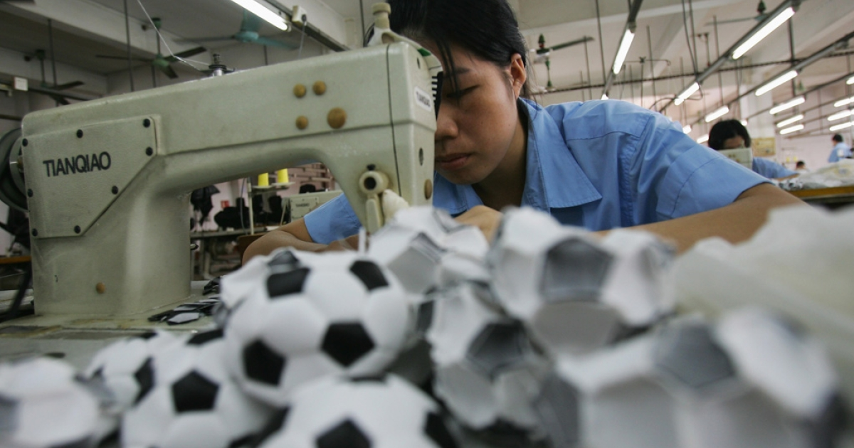 A worker assembles small soccer balls at the production line of Ball Star Toys Co., Ltd. in Guangzhou on Sept. 4, 2007 in Guangzhou, China.</p>
