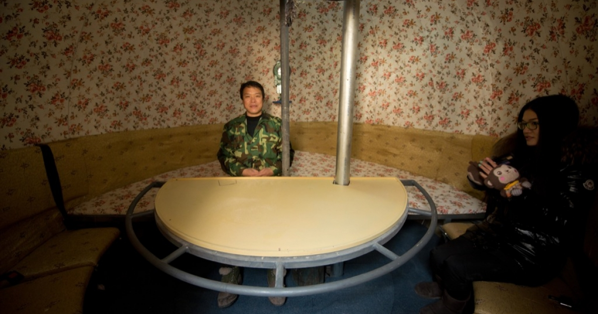 Farmer Liu Qiyuan (C) and his daughter sit inside one of seven survival pods that he has also dubbed 'Noah's Arc', in a yard at his home in the village of Qiantun, Hebei province, south of Beijing on December 11, 2012. Inspired by the apocalyptic Hollywood movie '2012' and the 2004 Asian tsunami, Liu hopes that his creations consisting of a fibreglass shell around a steel frame will be adopted by government departments and international organisations for use in the event of tsunamis and earthquakes.</p>