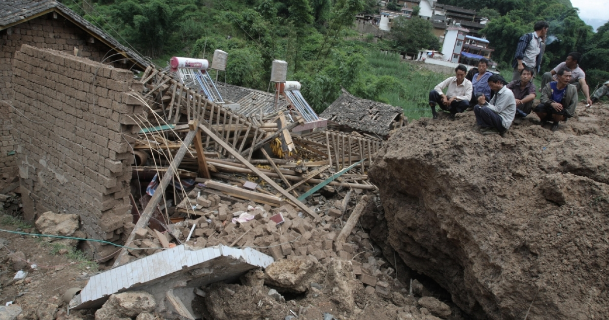 Chinese villagers sit beside their destroyed homes after landslides swept through a mountain village near the city of Baoshan in a rugged region of southwest China's Yunnan province on September 3, 2010.</p>