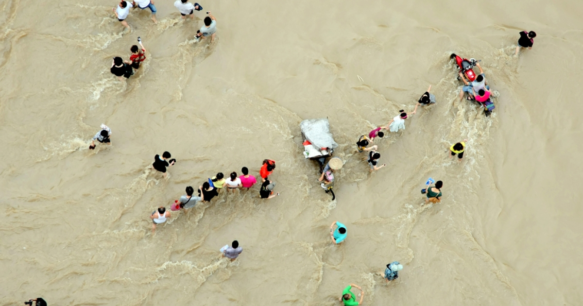 People make their way through flood water in Lanxi, in eastern China's Zhejiang province on June 20, 2011.</p>