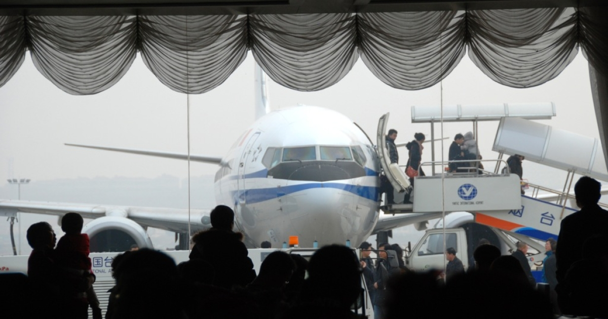 Passengers watch as a Chinese passenger plane unloads travellers at the airport in Yantai, in eastern China's Shandong province on February 6, 201. China said it has banned its airlines from complying with an EU scheme to impose charges on carbon emissions opposed by more than two dozen countries including India, Russia and the United States.</p>
