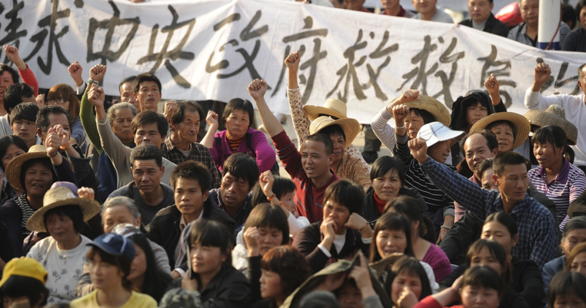 Residents of Wukan, a fishing village in the southern province of Guangdong, rally to demand the government take action over illegal land grabs and the death in custody of a local leader on Dec. 15, 2011.</p>