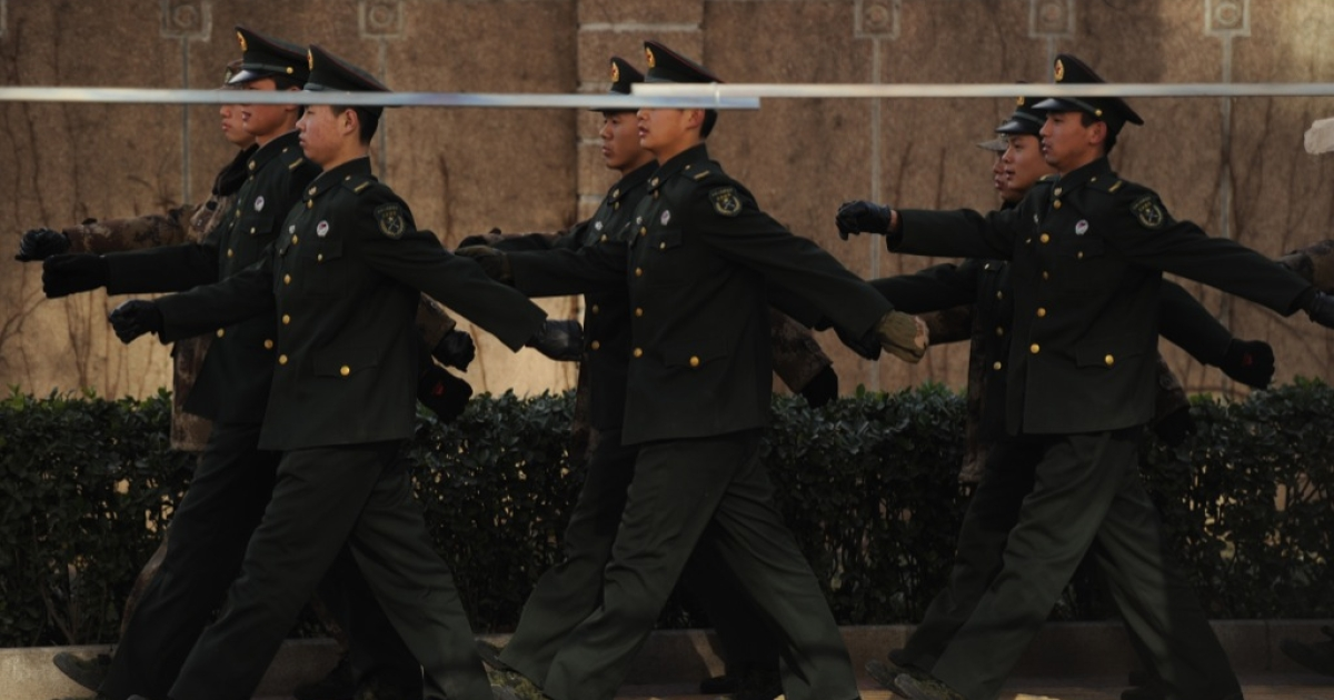 PLA soldiers march in front of the apartment complex where jailed Nobel peace laureate Liu Xiaobo's wife lives in Beijing on December 10, 2010.</p>