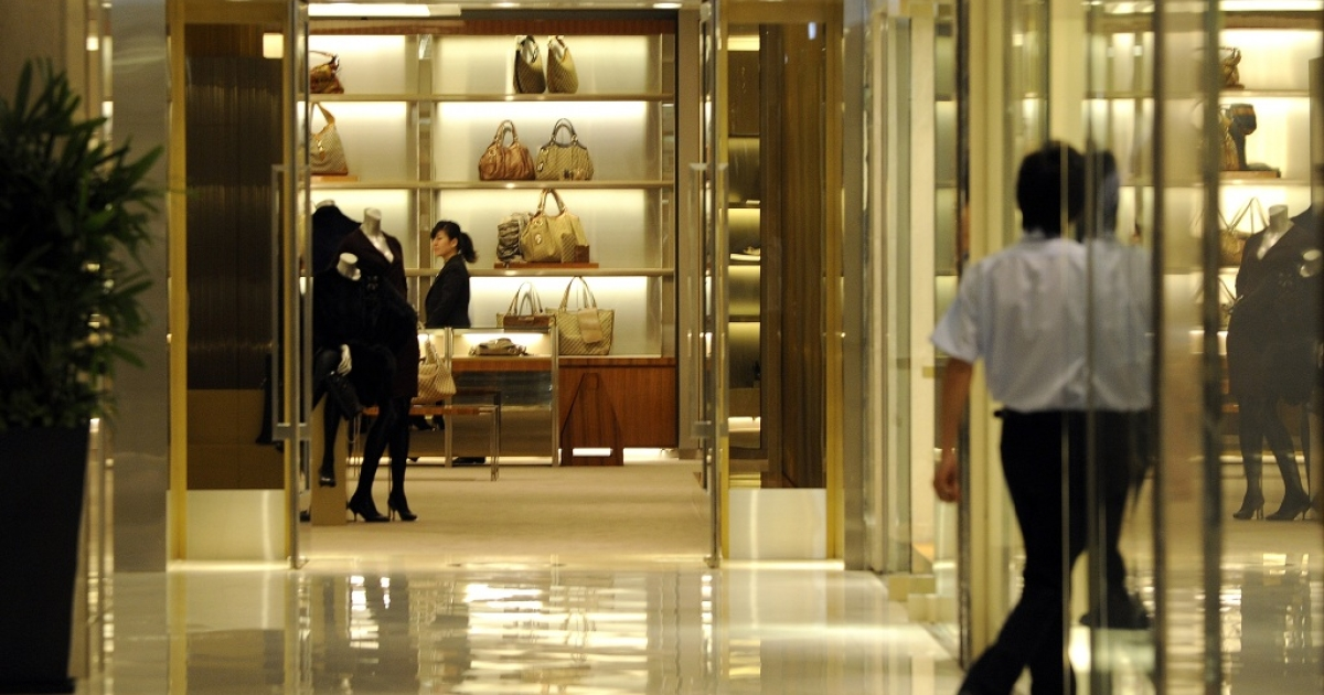 A saleswoman waits for the customers at a luxury Gucci fashion boutique in Beijing on September 5, 2010. China has vowed to make it easier to import goods into its huge market as Beijing seeks to address controversial trade surpluses with its trading partners, a report said on September 6.</p>