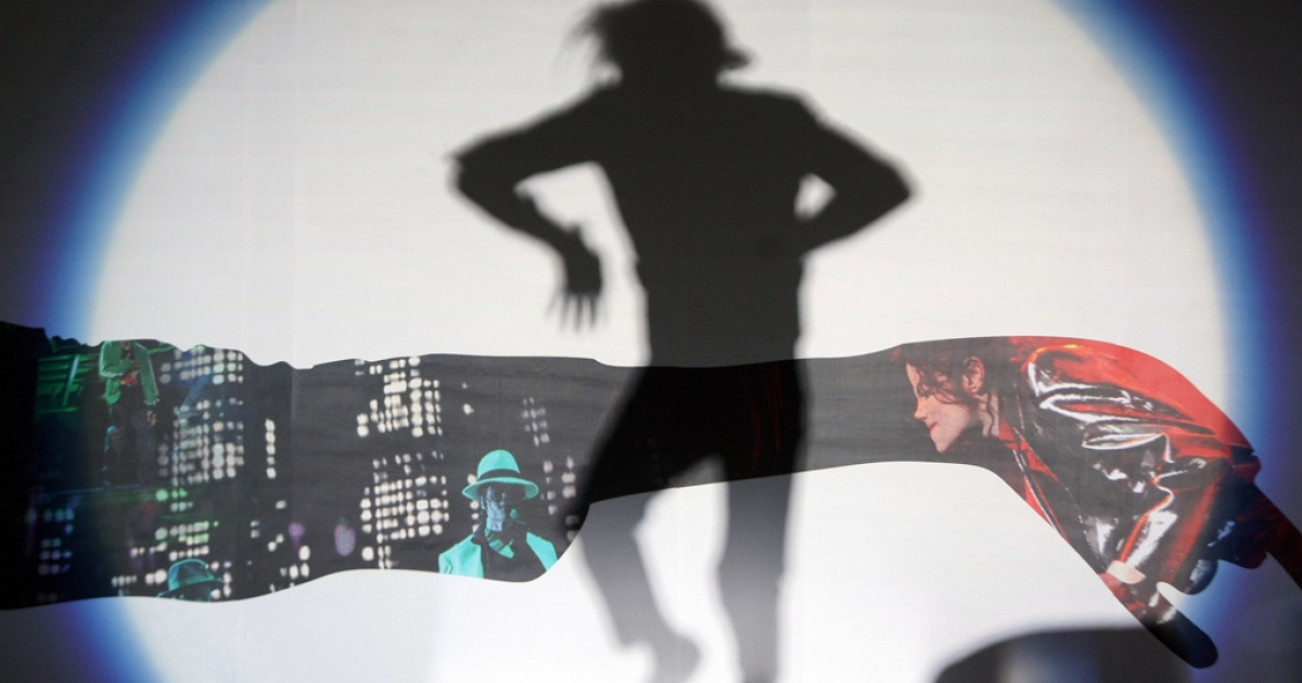 The shadow of a Michael Jackson impersonator from China is cast as he performs for thousands of fans gathered outside the Saga Cinema in Beijing on October 27, 2009.</p>