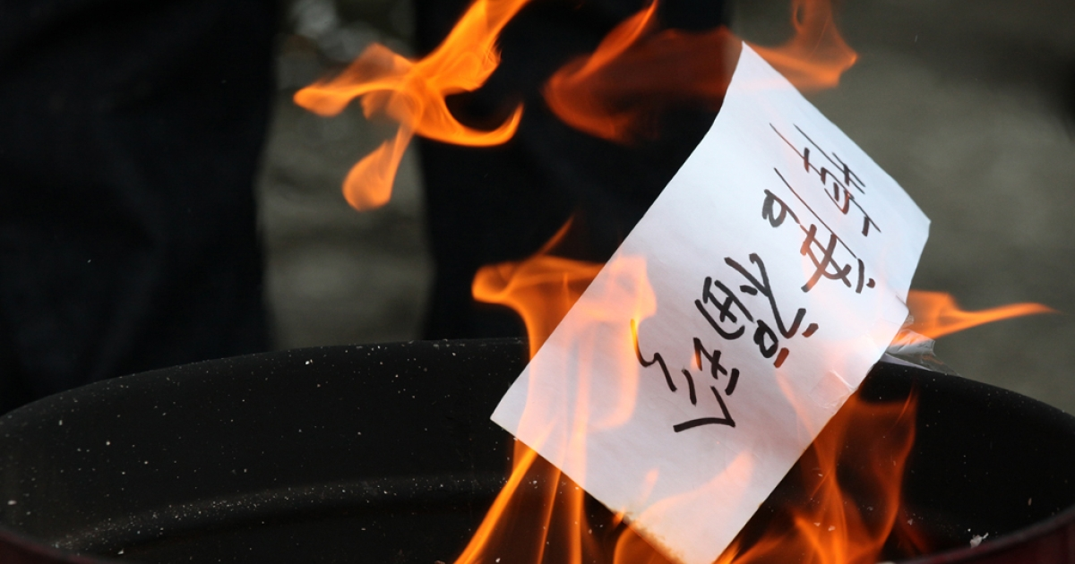 Paper money is burnt during a protest outside the Chinese liason office in Hong Kong on April 3, 2011. The protesters were supporting mainlanders after the government on March 29 formally arrested two activists on charges of