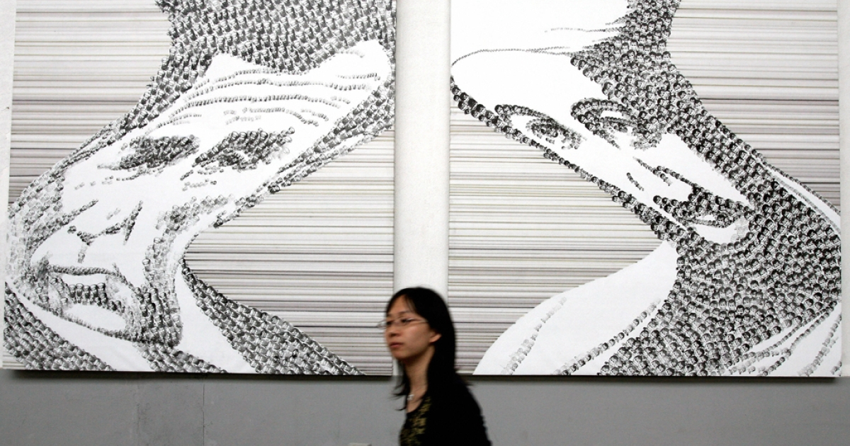 A Chinese visitor walks past an artwork of U.S. President George W. Bush and Osama bin Laden, the now-deceased leader of Al Qaeda, in Beijing on May 6, 2007.</p>