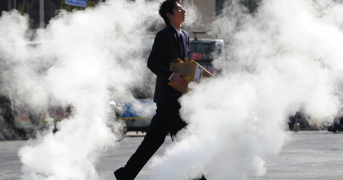 A businessman runs across a street as steam is emitted from underground on a cold winter's day in Beijing on Jan. 20, 2011.</p>