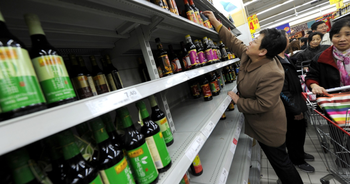 A woman stretches to get a bottle of soy sauce on the shelf after salt sold out early at a supermarket in Beijing on March 17, 2011.</p>