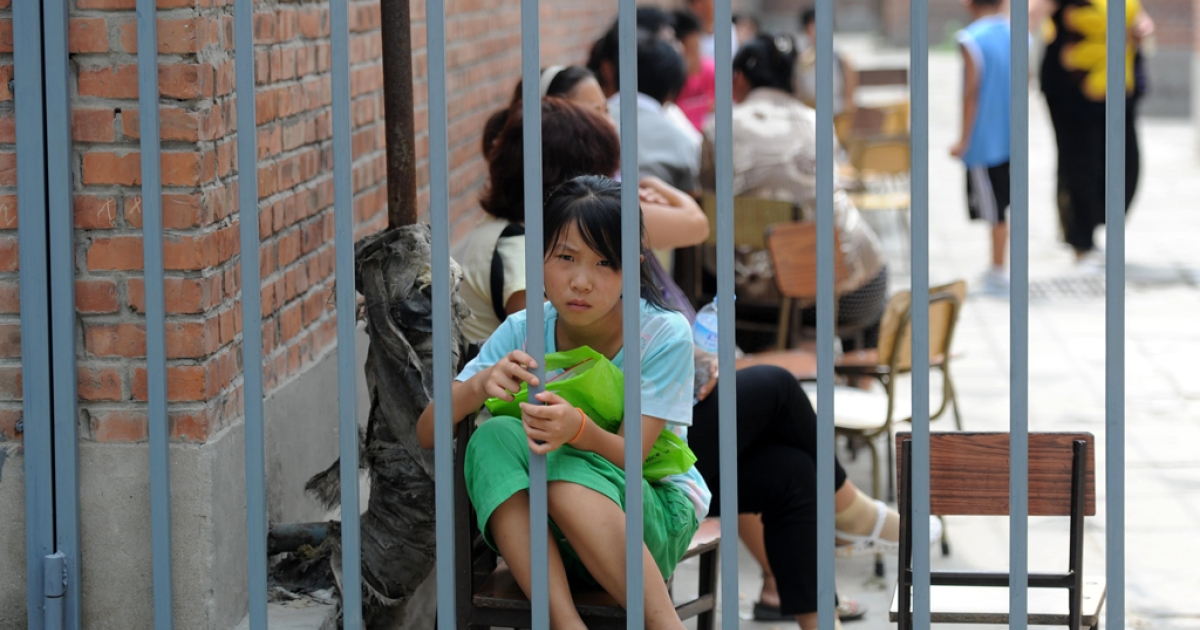 A Chinese girl waits outside a school in the suburbs of Beijing on Aug. 10, 2010.</p>