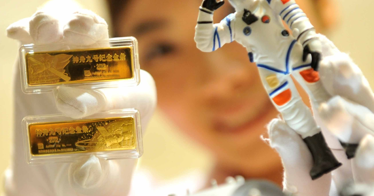 A worker shows a pair of gold bars to mark the launching of China's Shenzhou-9 spacecraft in Beijing.</p>