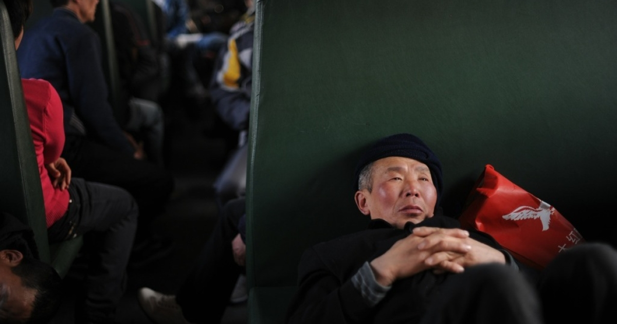 Chinese passengers wait in a train, which is specially offered for migrant workers by local government, to depart at a railway station in Beijing on January 8, 2011, as they return home for the lunar Chinese New Year holiday.</p>