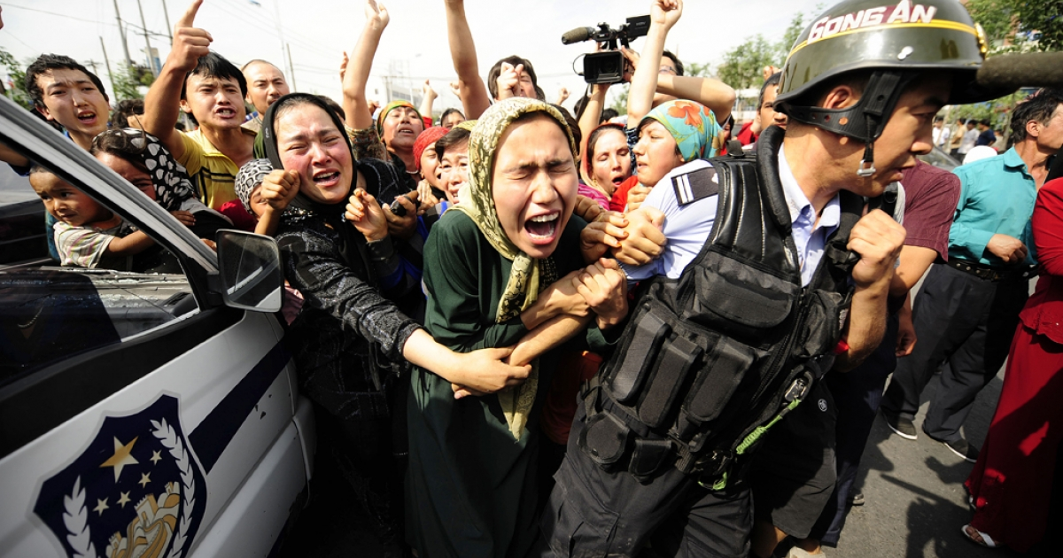 Ethnic Uygur women grab a riot policemen as they protest. Protests by ethnic Uygurs in the summer of 2009 lead to the deployment of thousands of heavily armed police in China's far west Xinjiang</p>