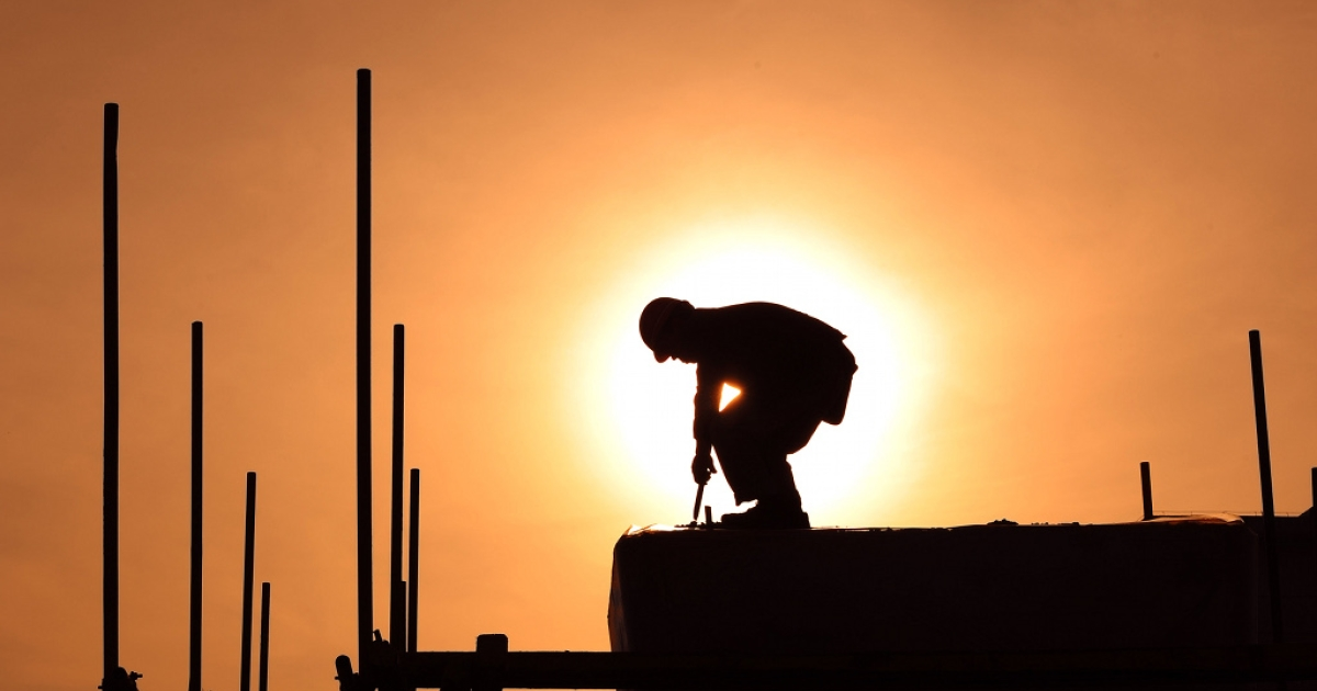 A woker stands before the sun at a construction project in Hefei, east China's Anhui province on April 23, 2011.</p>