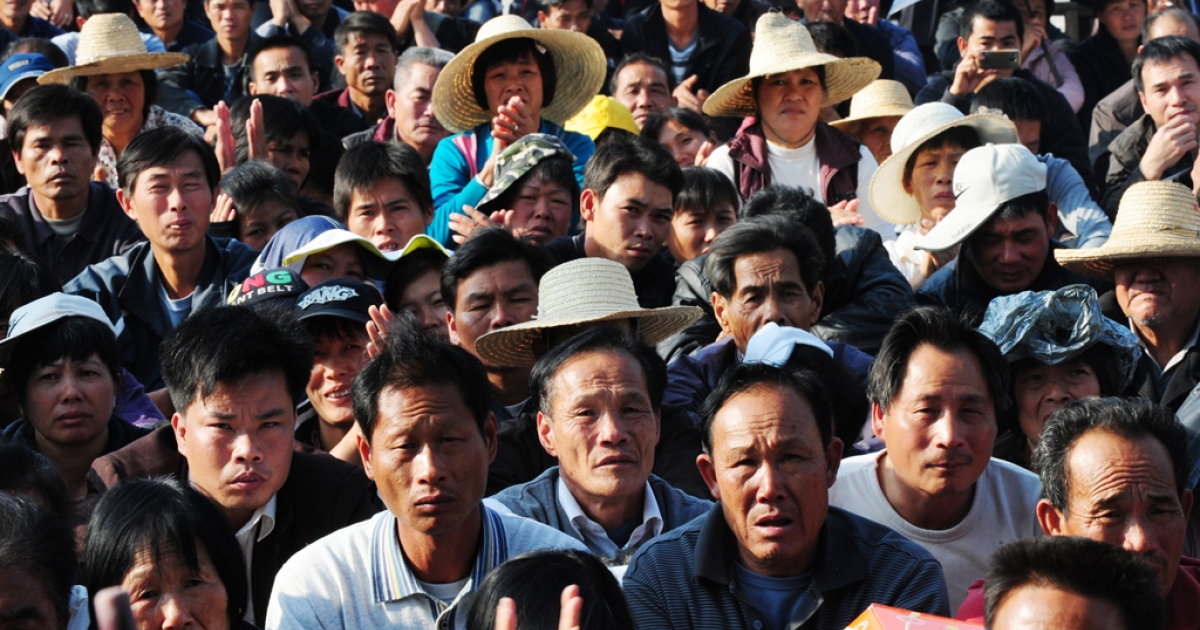 Villagers listen to a speech by village leader Lin Zulian at a rally in Wukan, Guangdong province, China, Dec. 21, 2011.</p>
