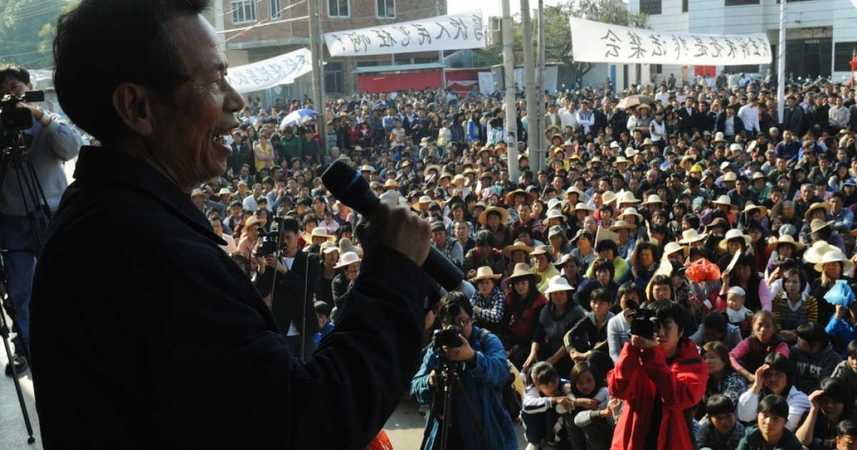 Villagers listen to a speech by village leader Lin Zulian (L) at a rally after he met with a senior government official and reached an agreement over illegal land grabs and the death in custody of a local leader in Wukan, Guangdong Province on December 21, 2011. Chinese authorities have agreed to release three villagers detained for leading September protests against land grabs, a community spokesman said December 21 after meeting a senior official.</p>