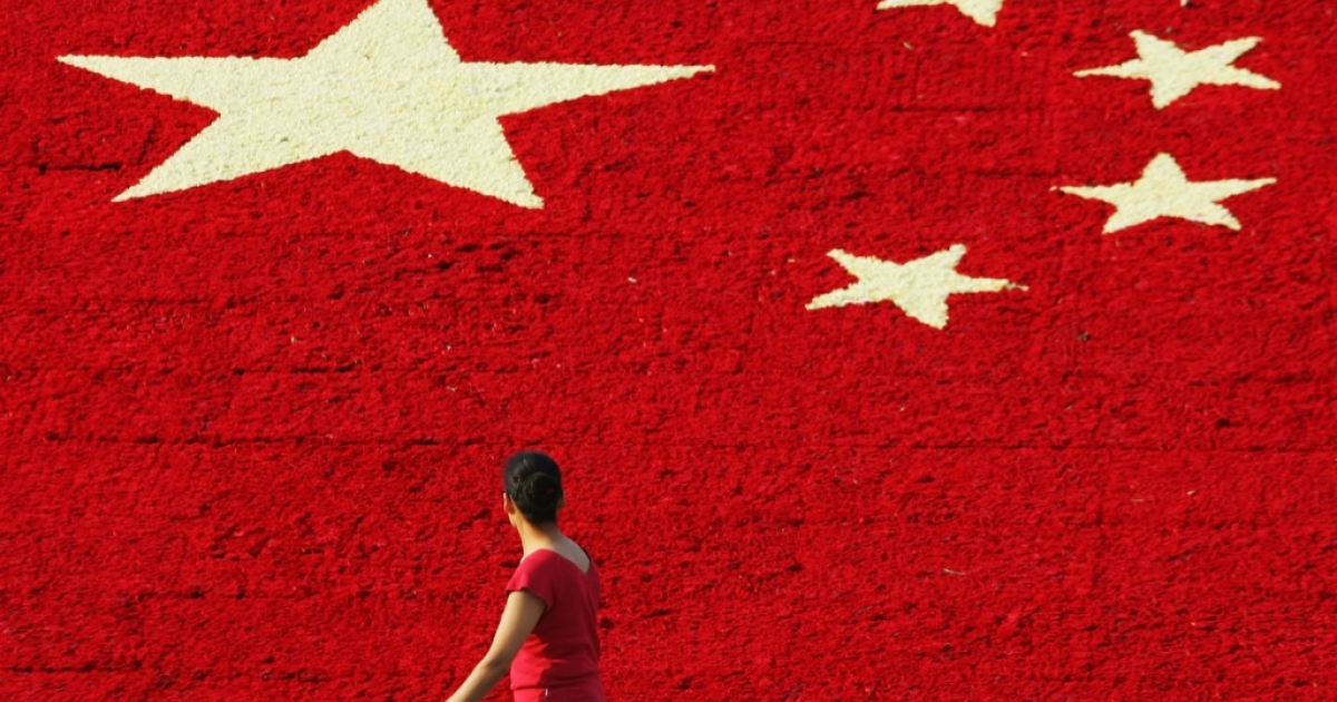 A woman passes by the national flag made up of 100,000 carnations at Wuling Square September 25, 2007 in Hangzhou, China.</p>