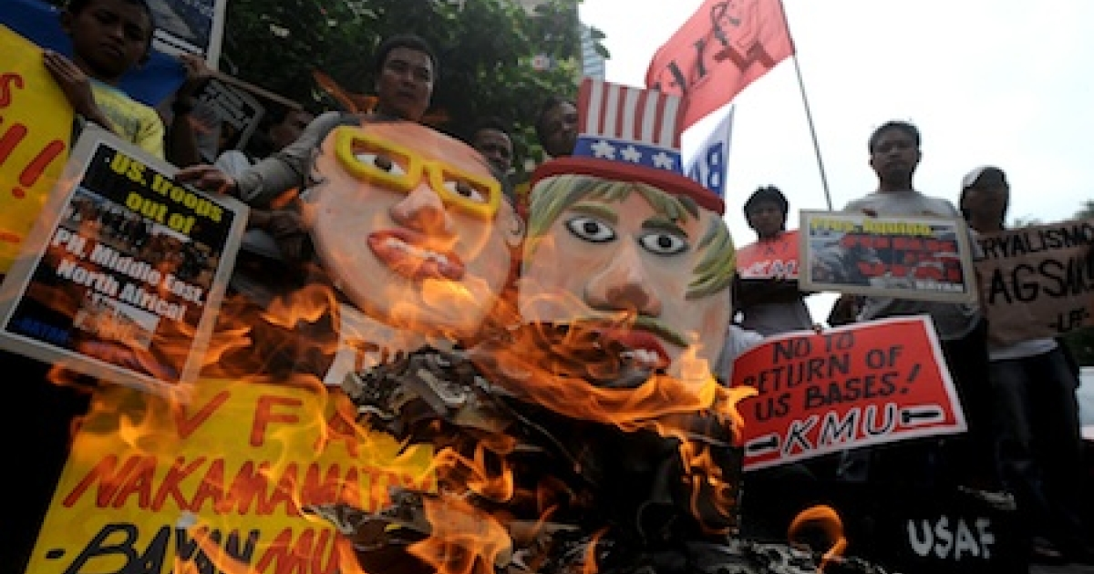 Filipinos burn a US flag and a mock US stealth bomber while holding an effigy of Philippine President Benigno Aquino and Uncle Sam during a protest in front of the US embassy in Manila on January 28, 2012. The activists picketed the US embassy as they vowed to launch a campaign opposing the planned increased US military role in the Philippines.</p>