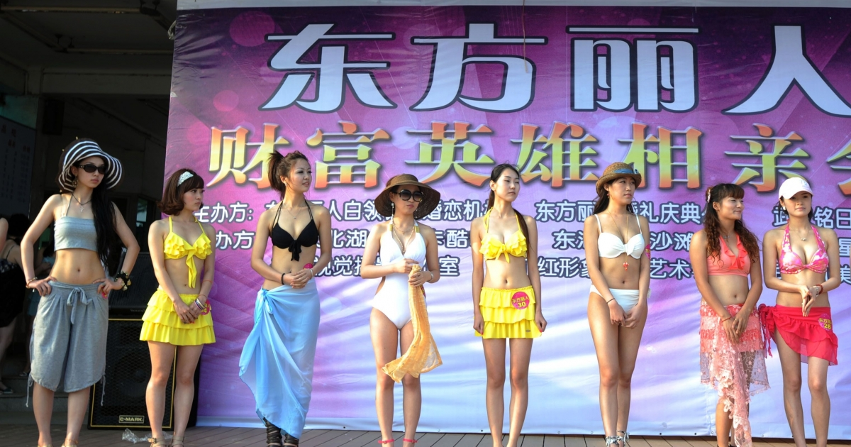 A group of Chinese women parading in their bikinis during a matchmaking event for wealthy men, with assets over 30 million yuan or make over one million yuan in annual income, on June 25, 2011 at the East Lake beach in Wuhan, central Hubei province.</p>