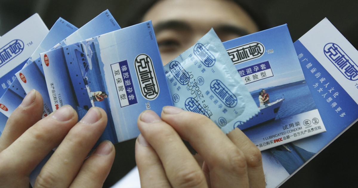 A worker displays 'Clinton' brand condoms produced by the Guangzhou Haojian Bio-science Co during a promotion in Guangzhou, Guangdong province, China.</p>