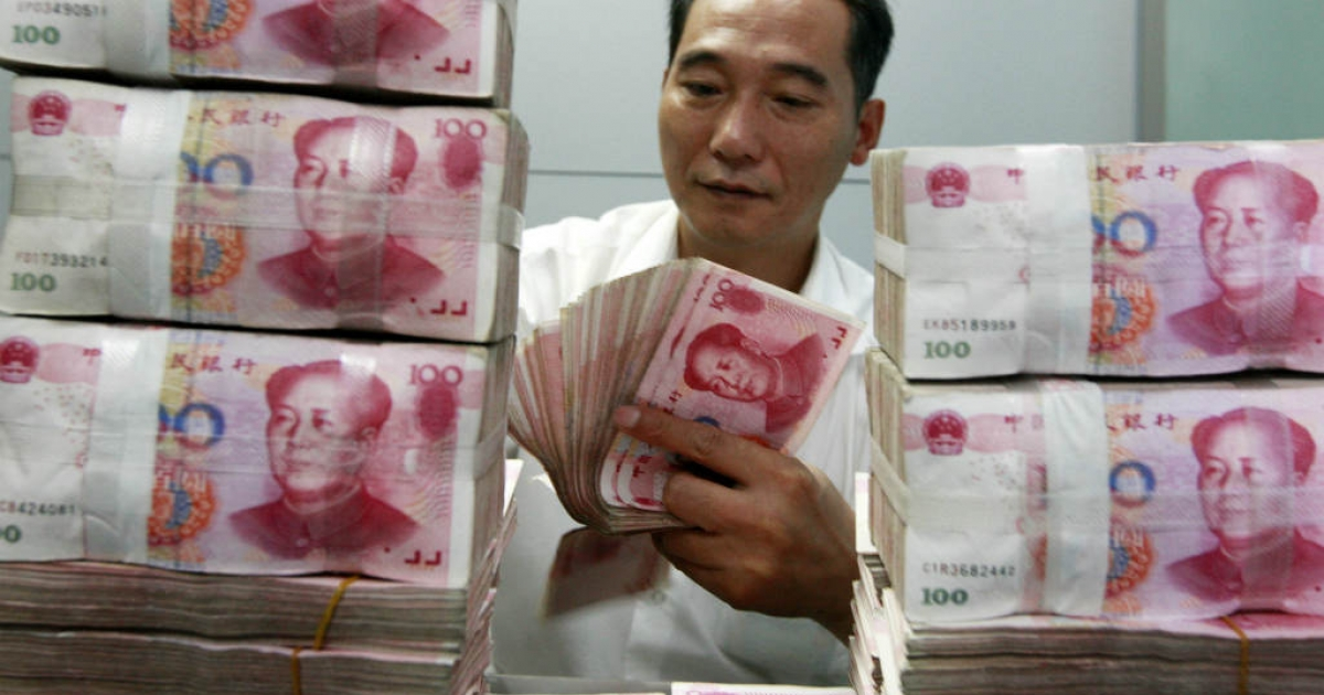 A Chinese bank staff member counts stacks of 100-yuan notes. Many U.S. policymakers believe that China manipulates its currency.</p>