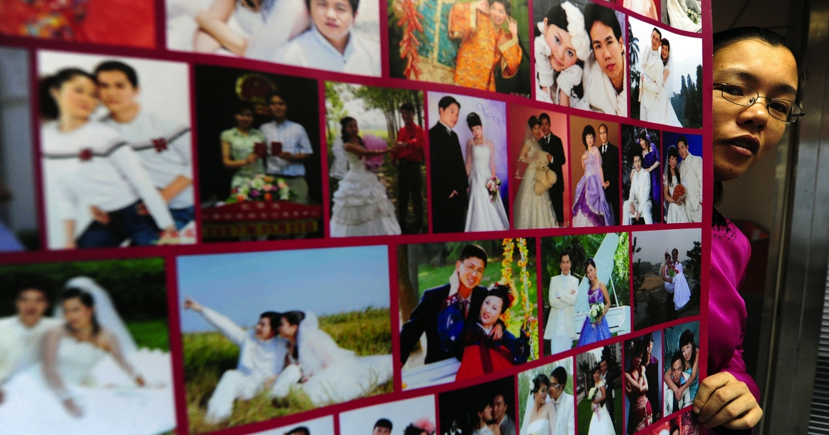 The founder of a Chinese internet dating site poses in Beijing beside a poster of photographs of married couples who met on her website. A winning contestant on the TV dating show