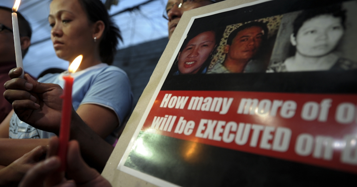 Mirasol Delfinado (L), sister of Sally Villanueva, one of three Filipinos executed in China after being convicted of drug trafficking offences, with supporters holds candles and placards outside their family home in Manila on March 30, 2011. The executions came after repeated pleas by the Philippine government for their sentences to be commuted were turned down, and ended vigils in Manila where supporters of the trio had prayed for a miracle.</p>