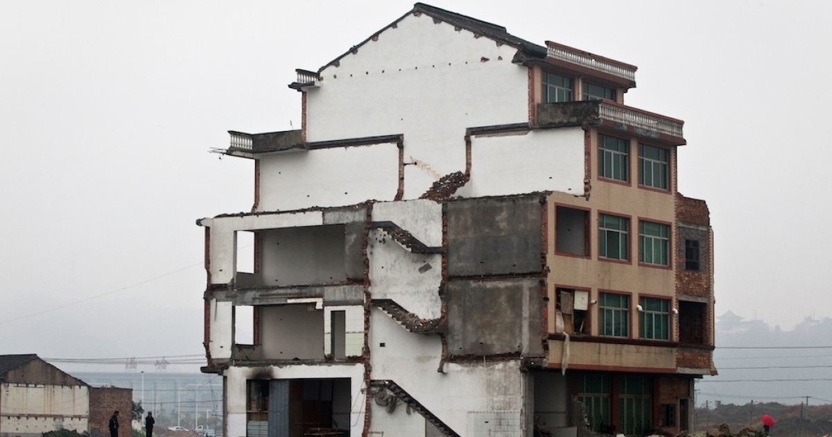 A half-demolished apartment building standing in the middle of a newly-built road thanks to a Chinese couple that refused to move in Wenling, in eastern China's Zhejiang province, on Nov. 22, 2012.</p>