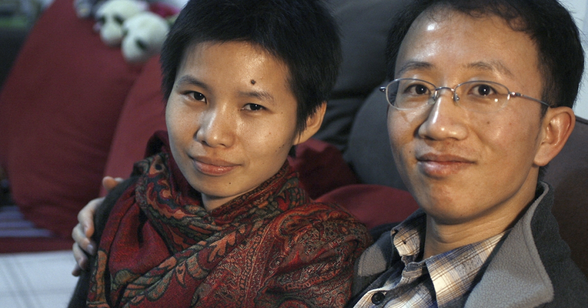 This file photo taken on January 9, 2007 shows Chinese human rights activists Hu Jia (R) and his wife Zeng Jinyan (L) in their apartment on the outskirts of Beijing. Zeng, the wife of jailed Chinese rights activist Hu Jia, who is due to be freed this weekend, has said on June 21, 2011 she is back in her Beijing home after being apprehended and taken to visit her husband in prison. Zeng said on her Twitter account that she was taken away by eight unidentified people after landing at Beijing airport on June 19, 2011, but then was allowed to meet with Hu at the prison on June 20, 2011. Hu is due to be released on June 26, 2011 after serving three and a half years for subversion.</p>