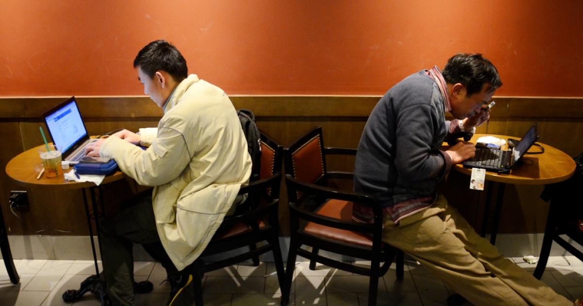 Two Chinese men use their laptop computers at a cafe in Beijing on November 2, 2012. The Lei Zhengfu sex tape may implicate more officials on charges of bribery and corruption.</p>