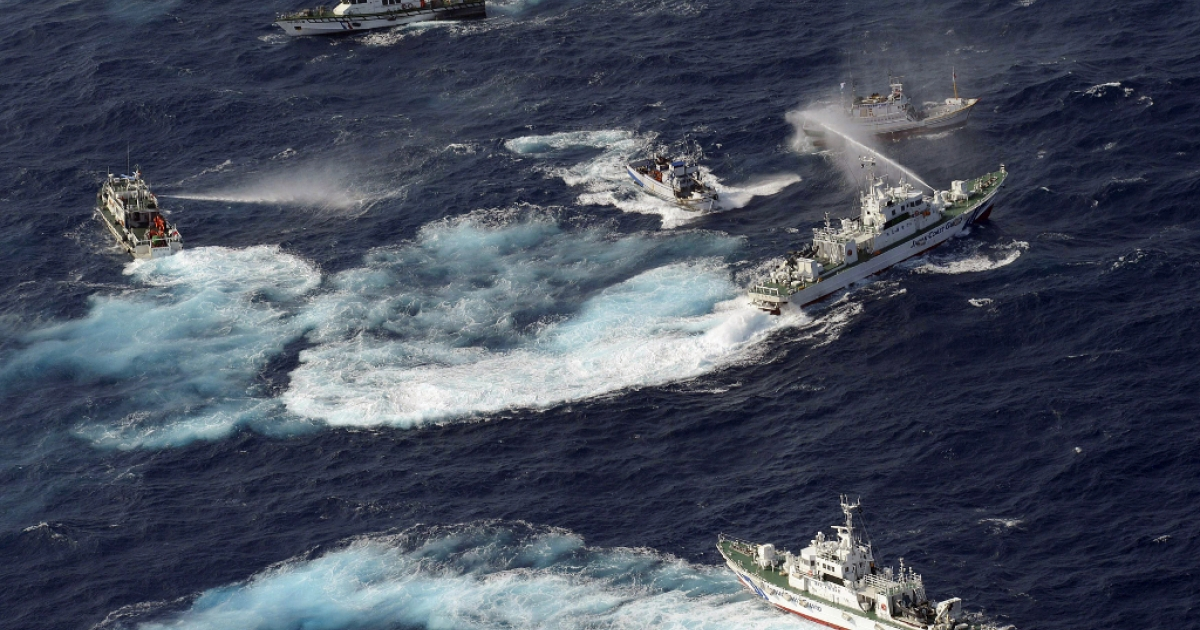 A Japan Coast Guard vessel sprays water against Taiwanese fishing boats, while a Taiwanese coast guard ship also sprays water in the East China Sea near Senkaku Islands as known in Japanese or Diaoyu Islands in Chinese on September 25, 2012.</p>