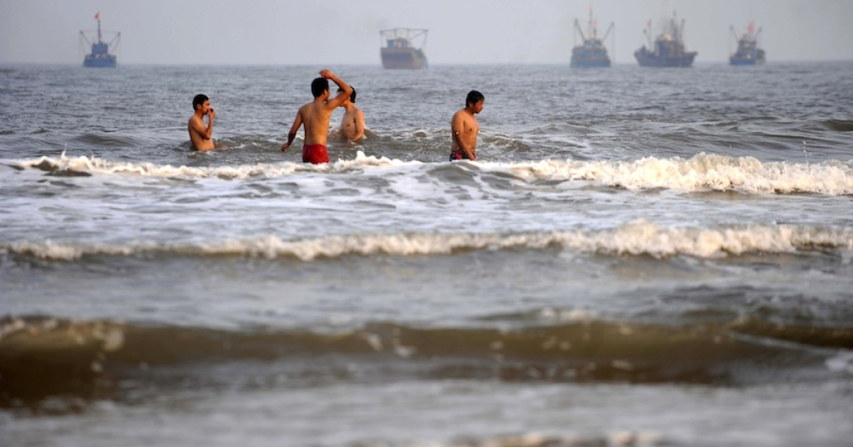 This photo taken on July 26, 2011 shows Chinese holidaymakers swimming off the country's northern coast despite oil sludge washed ashore by the spill in Bohai Bay.</p>