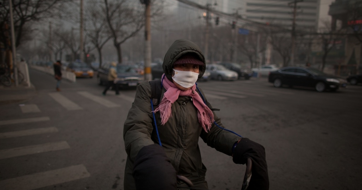 A cyclist wearing a mask prepares to cross a street during heavy pollution in Beijing on January 12, 2013.</p>