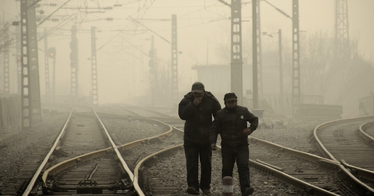This picture taken on Jan. 12, 2013, shows the dense smog in Beijing as two men walk along a railway line. The government is finally bowing to public outcry over the environmental situation in China.</p>