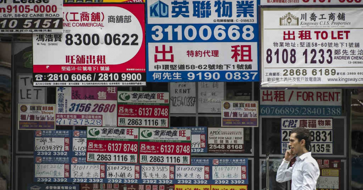 Billboards of real estate agents cover a wall in a street of Hong Kong..</p>