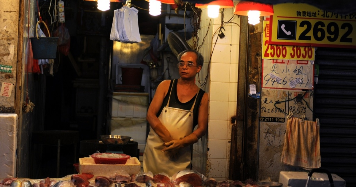 A man works inside a fresh seafood shop at a wet market in Hong Kong on June 26, 2012. The wealth gap in Hong Kong, already one of the world's widest, is worsening as the rich get richer and the poor struggle to make ends meet, official figures show.</p>