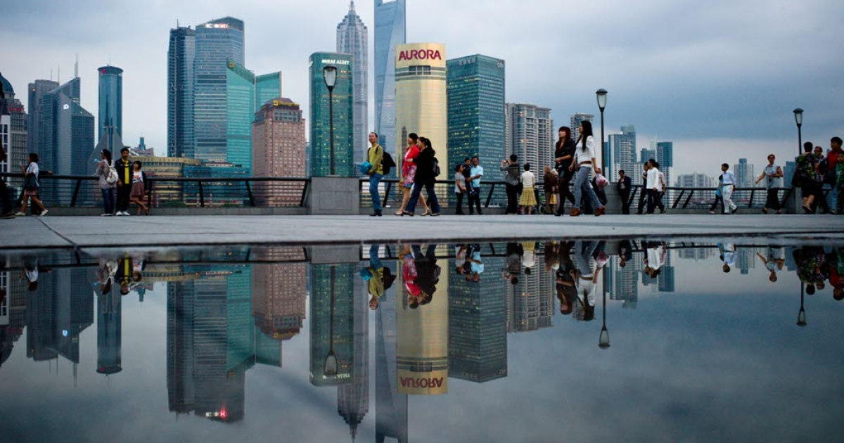 Pedestrians walk past the skyline of the city's financial district in Shanghai in October 2010.</p>