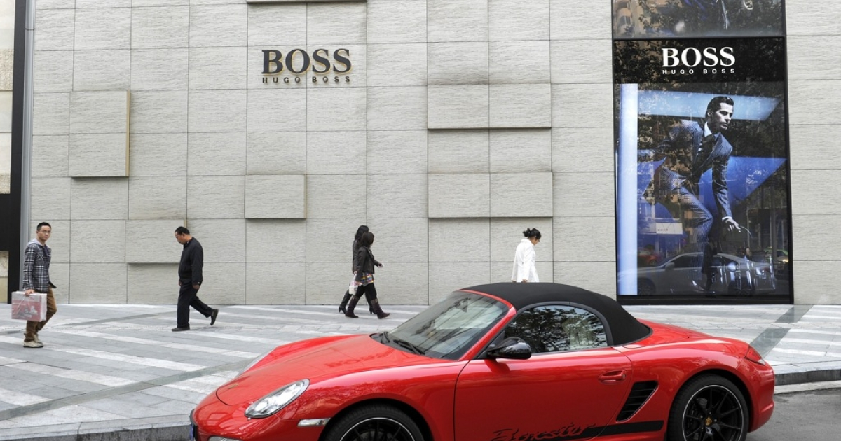Pedestrians walk in front of the fashion shop of Hugo Boss as a luxury sports car is parked nearby in Chengdu, the capital of China's southwestern province of Sichuan on November 23, 2011. China is forecast to be the world's top buyer of luxury products such as handbags, watches, shoes and clothes by 2015 and those living in smaller cities such as Chengdu in Sichuan province are driving the growth, analysts said</p>