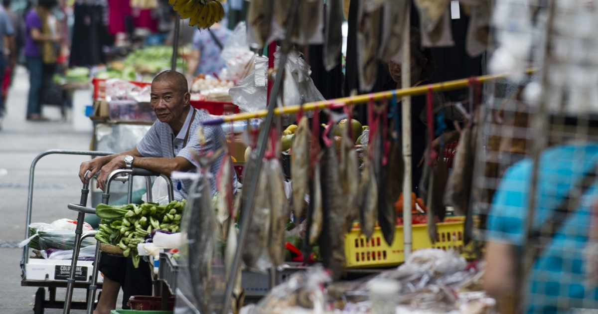 A vegetable stall owner waits at his street side shop in Hong Kong on October 9, 2012. The IMF cut its growth forecasts for developing Asia, blaming a slowdown in Europe and the US, and warned that China's attempts to boost its economy had not taken hold.</p>