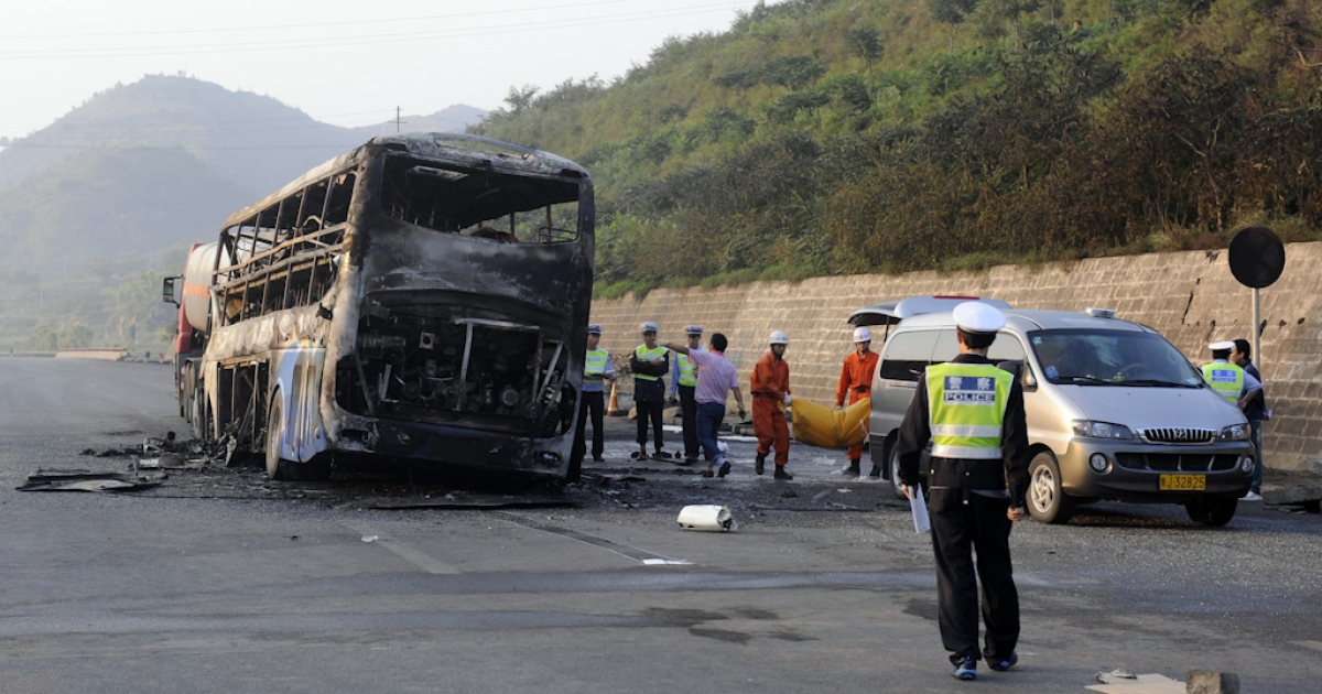 Police and rescuers remove the bodies from a burnt out double-decker sleeper bus after a collision with a tanker near Yan'an in northern China's Shaanxi province on August 26, 2012.  At least 36 people died in the fiery collision between a methanol tanker and a double-decker sleeper bus in China's worst traffic accident in more than a year</p>