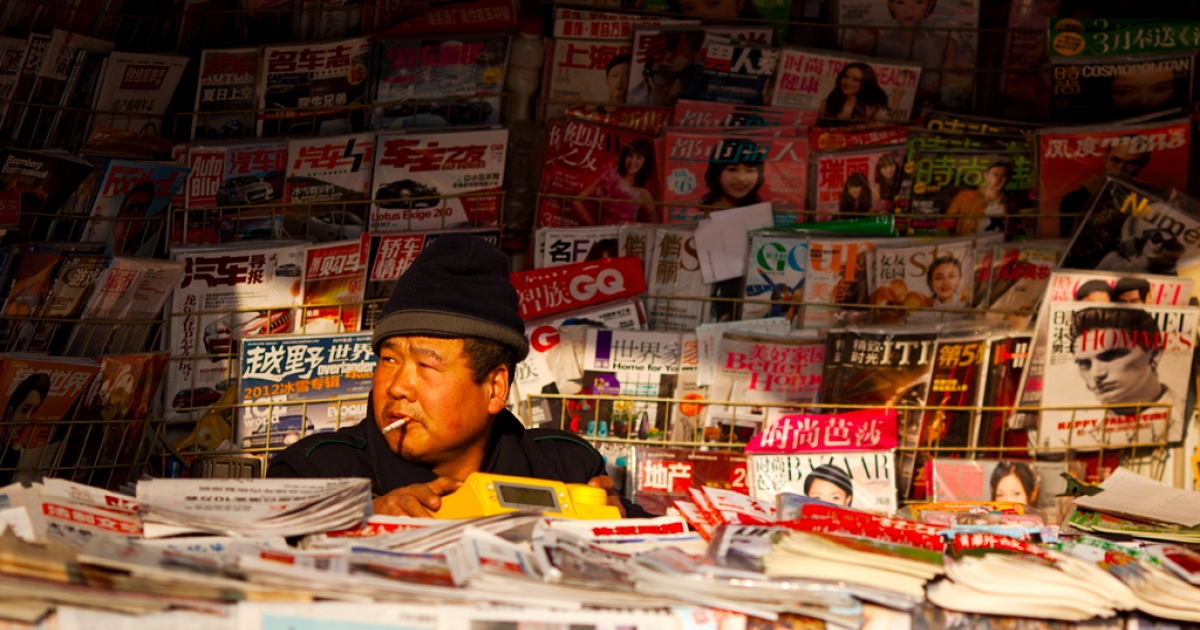 A photo taken on February 15, 2012 shows a vendor at his newspaper stand on a street in Beijing. Whilst China is using a great deal of financial and human means to improve its image abroad as a soft power, fingers are being pointed at those who it believes are the culprits of its negative image: the foreign press.</p>