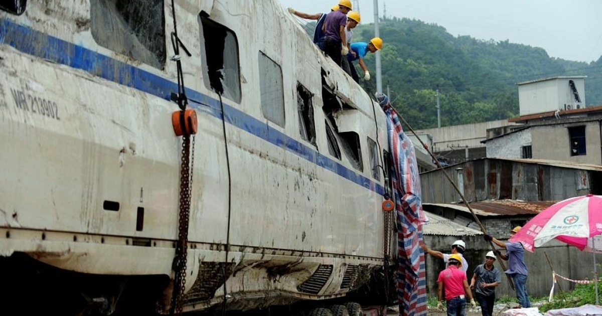 Workers prepare the wreckage of high-speed train carriage for transportation, two days after a fatal collision, in Shuangyu.</p>
